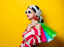 Style woman with shopping bags. Portrait of beautiful style woman in sunglasses and striped clothes with shopping bags on yellow background stock photo