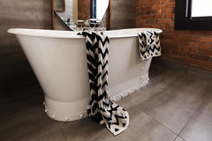 Styled bath towel draped over a freestanding vintage style bath. Tub royalty free stock photos