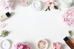 Styled beauty frame, web banner. Skin cream, shampoo, tonicum bottles, leaves, rose, peony flowers and salt on hite royalty free stock image