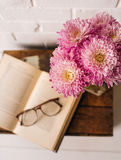 Styled Book and Flower Scene. A scene styled with an antique book, glasses, and pink flowers. All placed on an antique wooden box in front of a white brick wall Stock Images