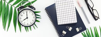 Styled design office workspace desk with camera. Top view flat lay office workspace desk styled design office supplies alarm clock tropical palm leaves stock images