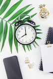 Styled design office workspace desk with camera. Top view flat lay office workspace desk styled design office supplies alarm clock tropical palm leaves royalty free stock photography