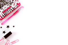 Styled desk photography in black, white and pink. A styled white desktop with a pink pen, lipstick, paper clips, stars, and a zebra print black and white Stock Photography