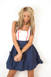 Styled Fashion. Young female fashion model with her hair styled big and she is wearing a white top with a high waisted blue skirt and standing against a white Royalty Free Stock Image