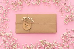 Styled feminine flat lay on pale pastel pink background, top view. Minimal woman`s desktop with blank page mock up, open envelope stock photography