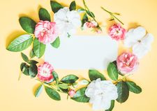 Styled feminine flat lay on pale pastel yello background, top view. Minimal woman`s desktop with blank page mock up, open envelope. Styled feminine flat lay on stock images