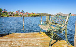 Styled iron bench on wooden bridge Royalty Free Stock Images