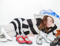 styled pretty little girl lying and enjoying her leisure time by choosing a new shoes to wear Stock Images