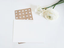 Styled stock photo. Feminine digital product mockup with buttercup and daffodil flowers, and blank list of paper . White Stock Photo