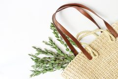 Styled stock photo. Feminine still life composition with straw French basket bag with long leather handles and. Eucalyptus branches on white backgouns, flat lay stock photos