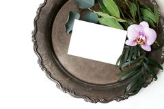 Styled stock photo. Feminine summer wedding still life composition, mockup scene. Closeup of vintage silver tray, blank. Card, orchid flower, bay laurel and royalty free stock image