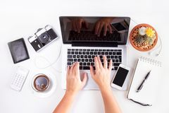 Styled workspace with laptop. Phone, notebbok and coffee, someones hands typing on keyboard, flat lay top view scene Royalty Free Stock Photos
