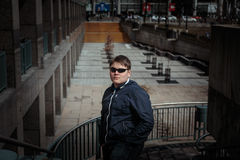 styled young adolescent in sunglasses standing against downtown city square park background Stock Photo
