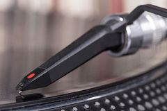 Stylet du DJ sur le vinyle de rotation, fond record Image stock