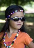 Styling. A young beautiful girl poses with sunglasses and beads. She displays a sense of power and determination stock photography