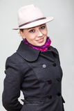 Styling Caucasian woman in coat and hat on grey Royalty Free Stock Images