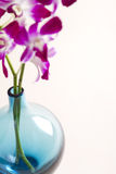 Stylised overhead image of vase and pink orchids. Overhead selective focus image with background area of blue vase and pink orchids Stock Photo