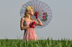 Stylish 1940's starlet in a field. Gorgeous blond vintage beauty standing in a tall grass with umbrella Stock Photography
