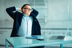 Stylish adult businessman while working day in office. Businessman with laptop, relaxing and smiling. Office interior with big win royalty free stock images