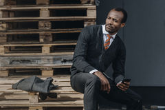 Stylish african american businessman using smartphone and sitting outdoors. Tired stylish african american businessman using smartphone and sitting outdoors Stock Image