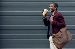 Stylish african american man with leather bag and coffee to go stock image