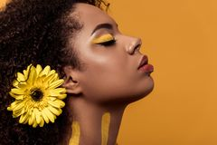 Stylish african american woman with artistic make-up and gerbera in hair dreaming. Isolated on orange background stock image