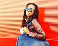 Stylish african woman in sunglasses with bag walking at city Stock Images