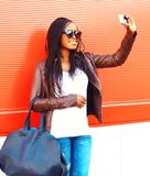 Stylish african woman taking self-portrait picture on smartphone Royalty Free Stock Images