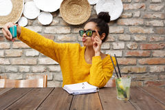 Stylish african woman taking selfie at cafe Stock Photography