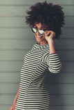Stylish Afro American girl. In sun glasses is looking at camera and smiling, on gray background Stock Photography