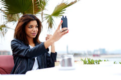 Stylish afro american woman taking self portrait with smartphone. Female tourist using mobile phone camera for take a picture of herself during vacation holidays Stock Images