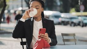 Stylish afro business woman using smartphone drinking coffee sitting on the summer terrace in cozy cafe. Communication stock footage