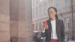 Stylish afro business woman using smartphone walking on the street near business centre. Black Stylish. Dreadlocks. Afro. Hairstyle stock video