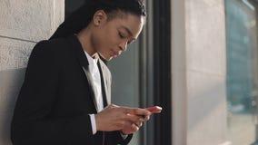 Stylish afro businesswoman using smartphone standing on the street near business centre. Black Stylish. Dreadlocks. Afro stock video