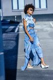 Stylish afro girl in jeans clothes and sunglasses walking. On street stock photography