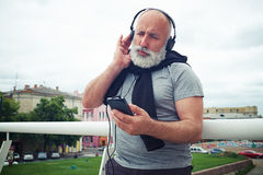 Stylish aged man in headphones enjoys music from smart phone Royalty Free Stock Photography