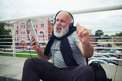 Stylish aged man in headphones joins in a song Royalty Free Stock Image