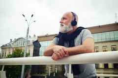 Stylish aged man in headphones leaning on handhold and musing. Stylish aged man in headphones is leaning on the handhold and musing in the city on a cloudy day royalty free stock photo