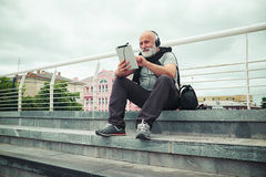 Stylish aged man in headphones scrolling something in tablet com Royalty Free Stock Photo