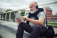 Stylish aged man in headphones with tablet computer sits on a si Royalty Free Stock Photos