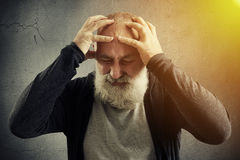 Stylish aged man is holding head with fingers against wall with Stock Photo