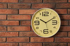 Stylish analog clock hanging on brick wall. Space for text royalty free stock images