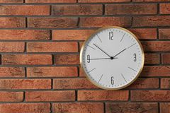 Stylish analog clock hanging on brick wall. Space for text royalty free stock photo