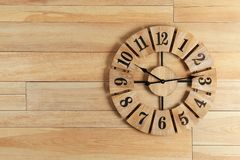 Stylish analog clock hanging on wooden wall. Space for text stock images