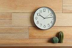 Stylish analog clock hanging on wooden wall. Space for text royalty free stock photo