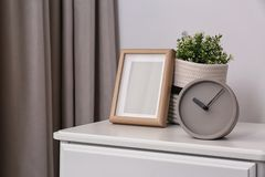 Stylish analog clock, photo frame and potted plant on chest of drawers in room. Space for text stock image
