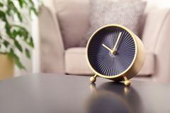 Stylish analog clock on table in living room, space for text. Time of day stock images