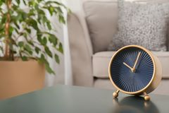Stylish analog clock on table in living room. Space for text. Time of day royalty free stock photos
