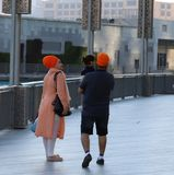 Stylish anonymous  family in orange turban out walking. Anonymous stylish family, orange turbans, walking in the park, enjoying sunshine Royalty Free Stock Photography