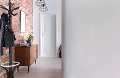 Stylish apartment hall clothes hanger, cupboard and brick wall, real photo. With copy space stock photo